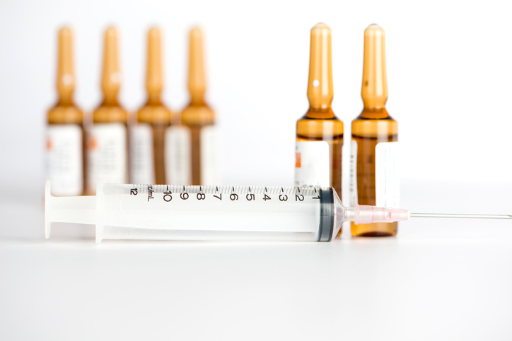 Injection syringe and brown ampule background